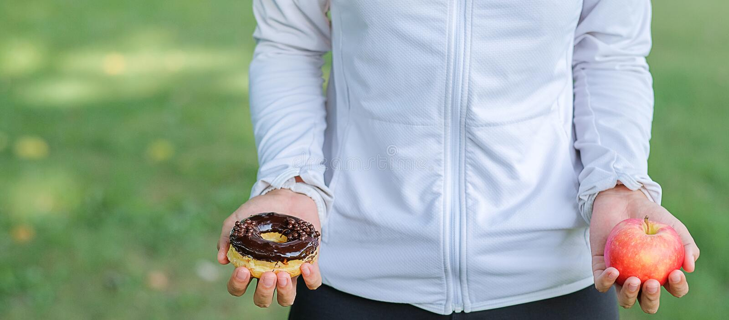 Jeune femme de forme physique se tenant dans des mains pomme et beignet rouges image libre de droits
