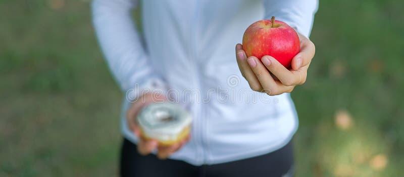 Jeune femme de forme physique se tenant dans des mains pomme et beignet rouges photo libre de droits