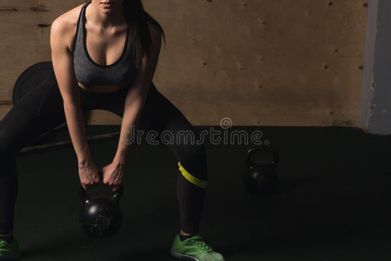 Jeune femme de forme physique soulevant la cloche lourde de bouilloire au gymnase photographie stock libre de droits