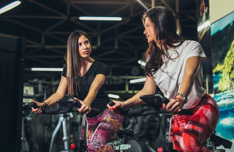 Jeune femme de forme physique sur le vélo de gymnase photo stock