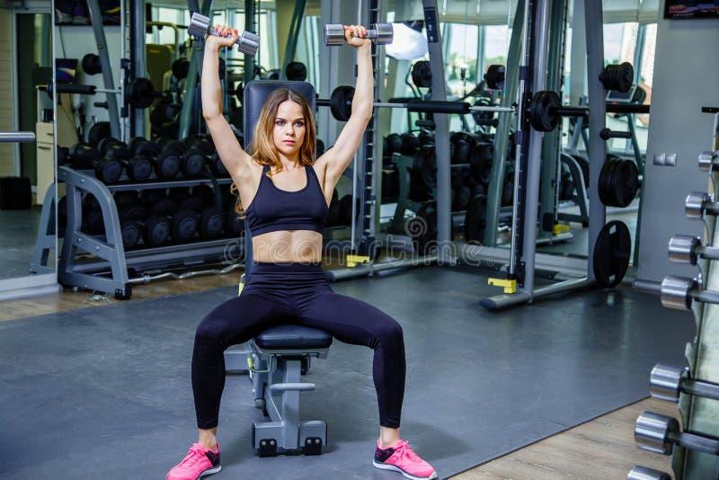 Jeune femme de forme physique tenant un poids de main photographie stock