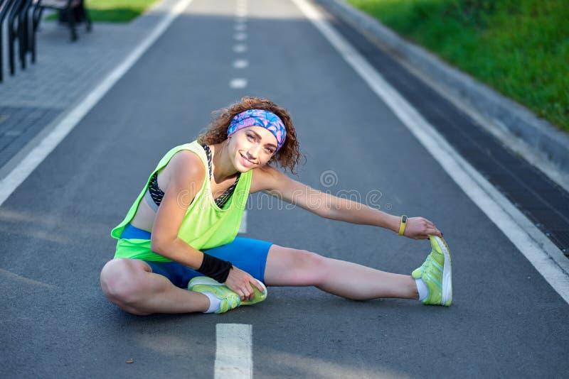 Jeune femme de forme physique ?tirant des jambes apr?s course dehors apr?s course image libre de droits