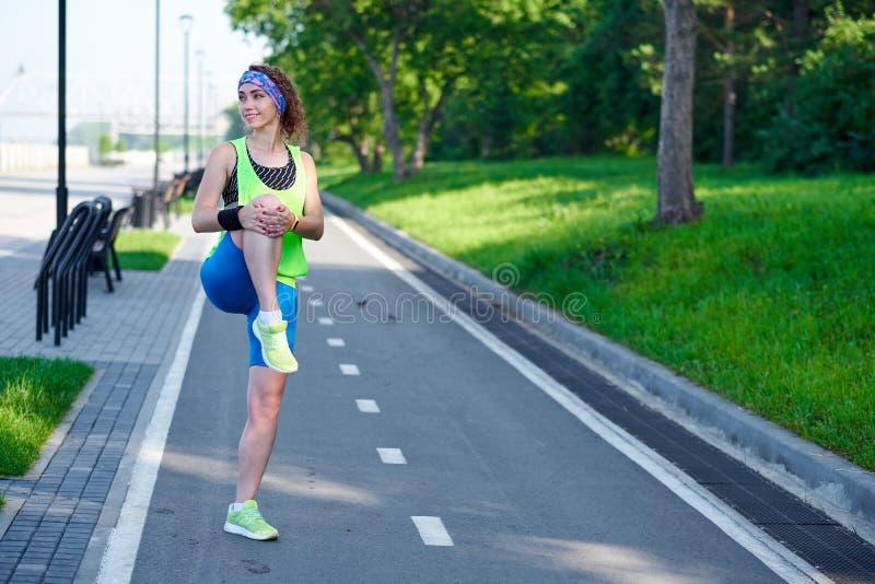 Jeune femme de forme physique ?tirant des jambes apr?s course dehors apr?s course photos libres de droits
