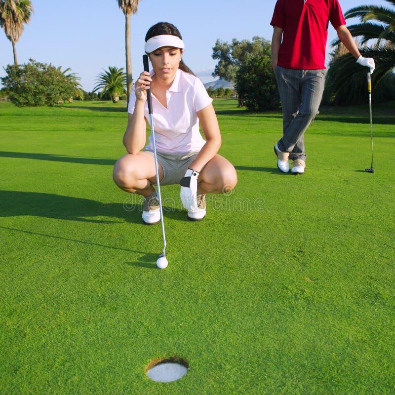 Jeune femme de golf regardant et orientant le trou photographie stock libre de droits