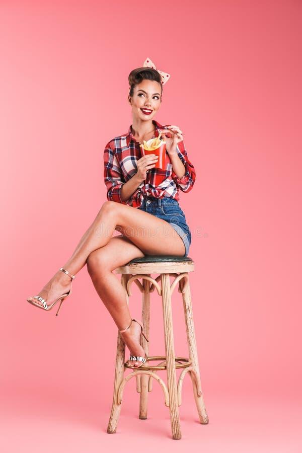Jeune femme de goupille- s'asseyant sur des selles photographie stock libre de droits