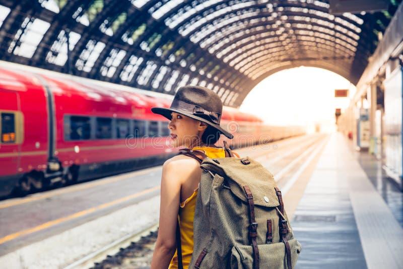 Jeune femme de hippie de randonneur attendant le train à la plate-forme images stock