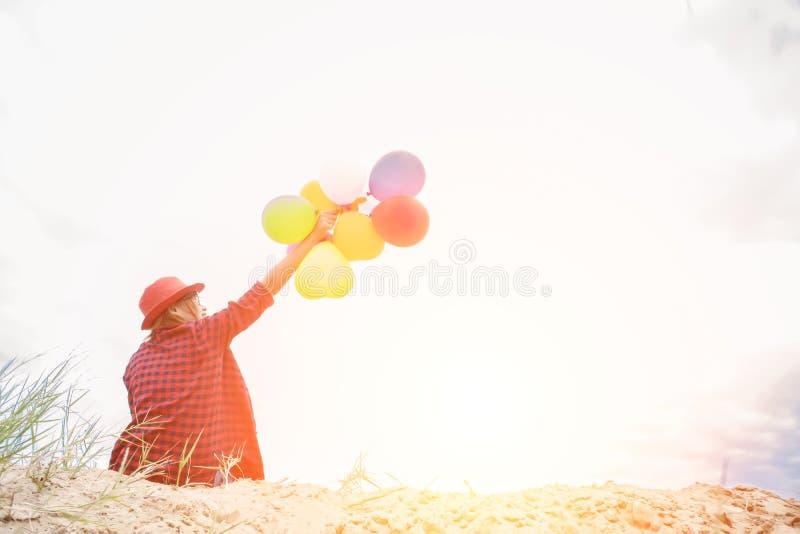 Jeune femme de hippie s'asseyant sur le sable et tenant BAL coloré photographie stock
