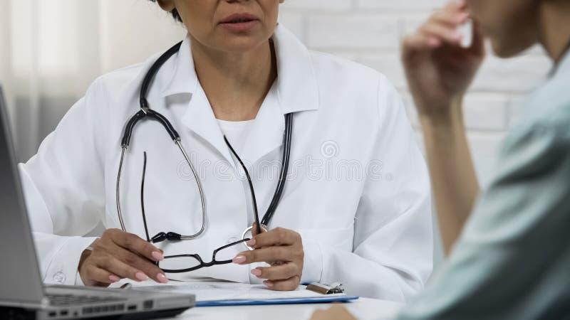 Jeune femme de information d'oncologiste au sujet de la maladie incurable, mauvaise nouvelle au sujet de tumeur images stock