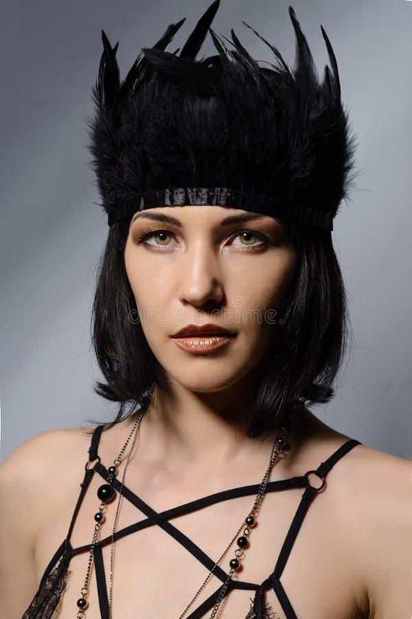 Jeune femme de luxe avec les plumes noires dans ses cheveux images stock