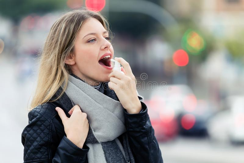 Jeune femme de maladie employant un pulvérisateur analgésique pour ramollir la gorge dans la rue photo libre de droits