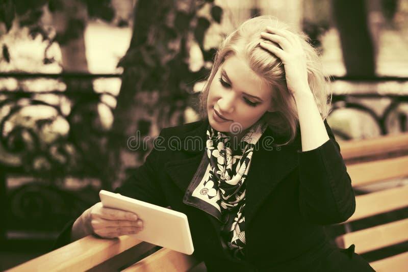 Jeune femme de mode avec la tablette se reposant sur le banc images libres de droits