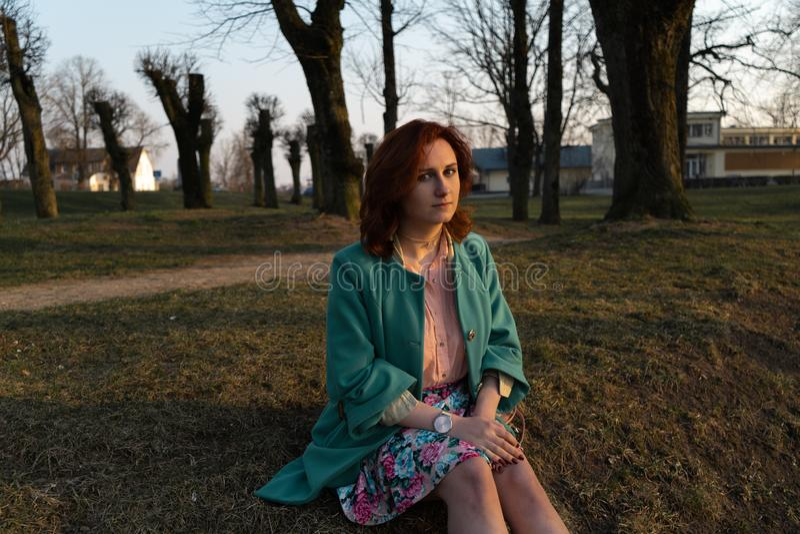 Jeune femme de mode détendant et appréciant le coucher du soleil près d'une rivière dans Bauska, Lettonie, 2019 image libre de droits