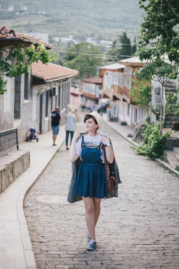 Jeune femme de mode dans un chapeau de paille et au-dessus du chandail tricoté classé posant dans une rue de ville photos stock