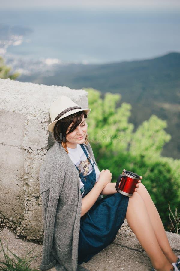 Jeune femme de mode s'asseyant sur un dessus du thé potable de montagne avec de belles montagnes et la vue d'océan sur le fond images stock