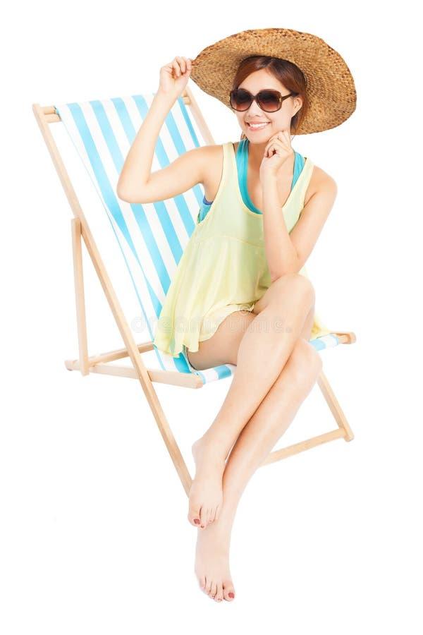 Jeune femme de mode souriant et s'asseyant sur une chaise de plage photographie stock libre de droits