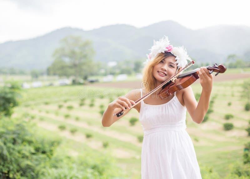 Jeune femme de musicien de hippie jouant le violon dans le mode de vie extérieur de nature derrière la montagne photo stock