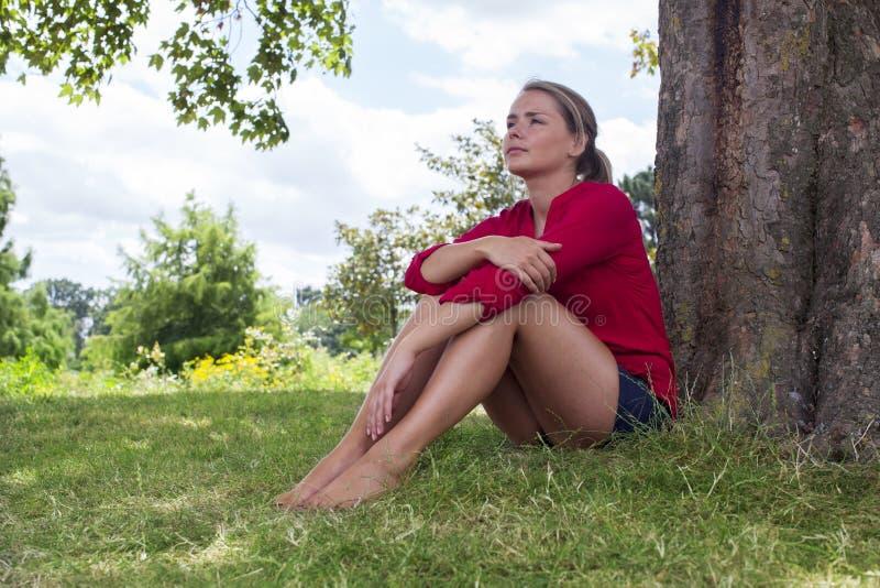 Jeune femme de pensée s'asseyant sous un arbre pour la fraîcheur d'été photographie stock