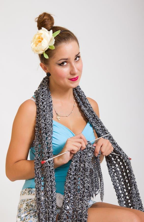 Jeune femme de pin-up tricotant une écharpe photos libres de droits