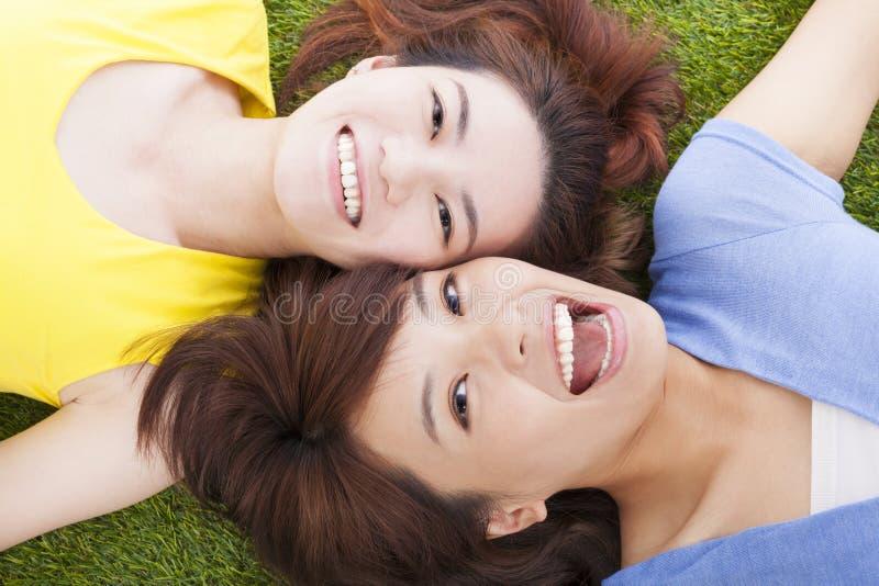 Jeune femme de plaisir de deux Asiatiques se trouvant sur l'herbe image stock