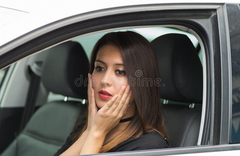 Jeune femme de plan rapproché s'asseyant dans la voiture agissant l'un sur l'autre légèrement choqué, comme vu de la fenêtre exté photos libres de droits