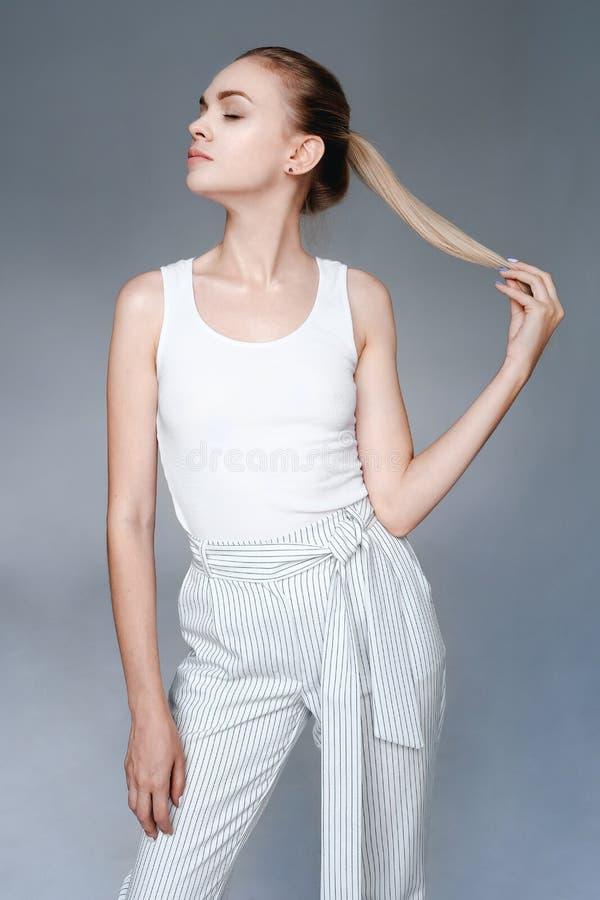 Jeune femme de portrait de mode de beauté avec la peau claire se tenant par les cheveux photographie stock libre de droits