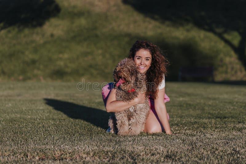 jeune femme de propriétaire avec son chien d'eau espagnol brun ayant l'extérieur d'amusement dans un parc au coucher du soleil Am photos libres de droits