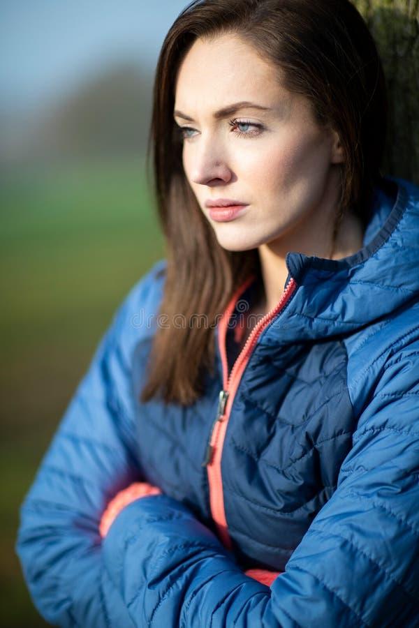 Jeune femme de regard malheureuse se penchant contre l'arbre sur la promenade d'hiver en parc photos libres de droits