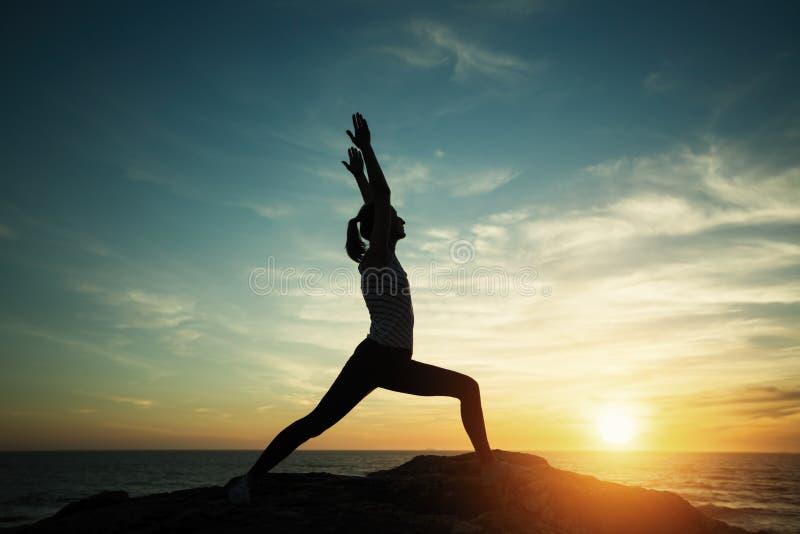 Jeune femme de silhouette de yoga faisant des exercices de forme physique sur la plage photo libre de droits