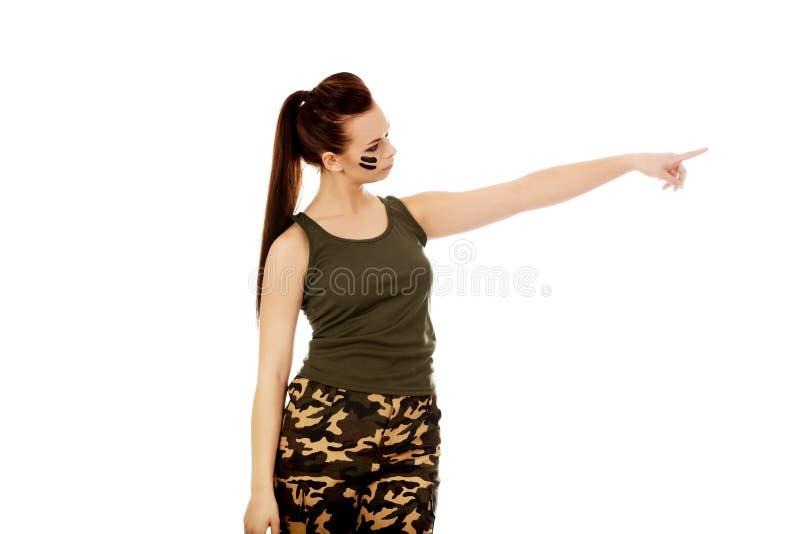 Jeune femme de soldat se dirigeant pour quelque chose photographie stock