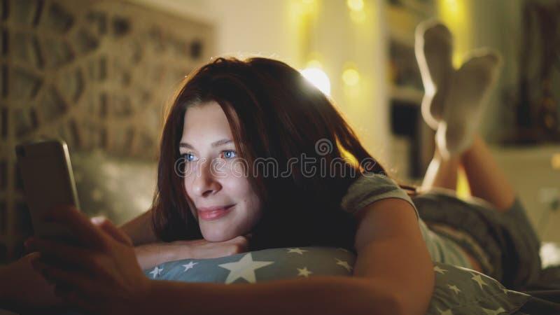 Jeune femme de sourire à l'aide du smartphone pour partager le media social se trouvant dans le lit à la maison la nuit image libre de droits