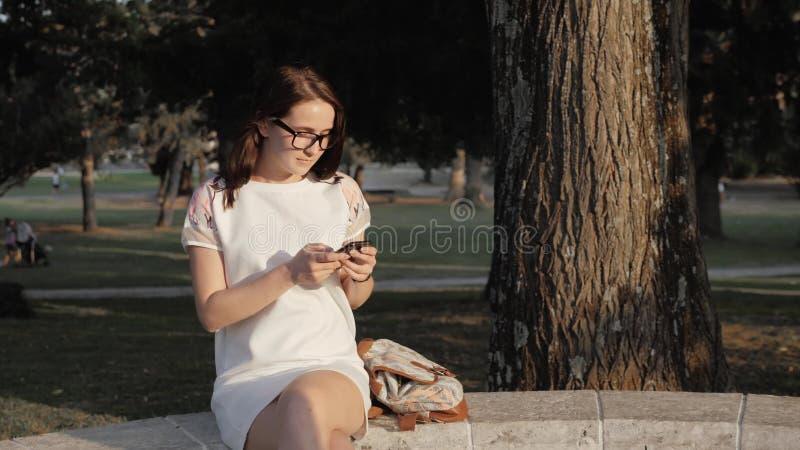 Jeune femme de sourire à l'aide du smartphone se reposant sur le banc dans le parc au coucher du soleil Beau service de mini-mess image libre de droits