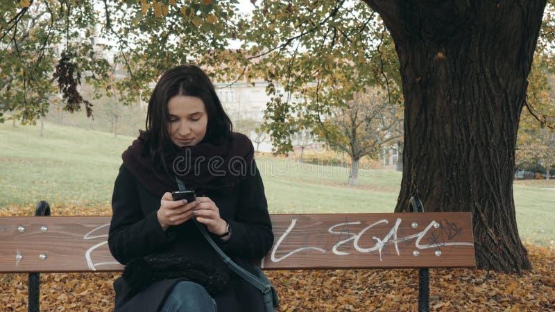 Jeune femme de sourire à l'aide du smartphone se reposant sur le banc dans le parc Beau service de mini-messages européen de fill photo libre de droits