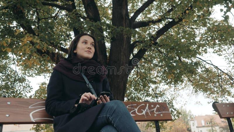 Jeune femme de sourire à l'aide du smartphone se reposant sur le banc dans le parc Beau service de mini-messages européen de fill photo stock