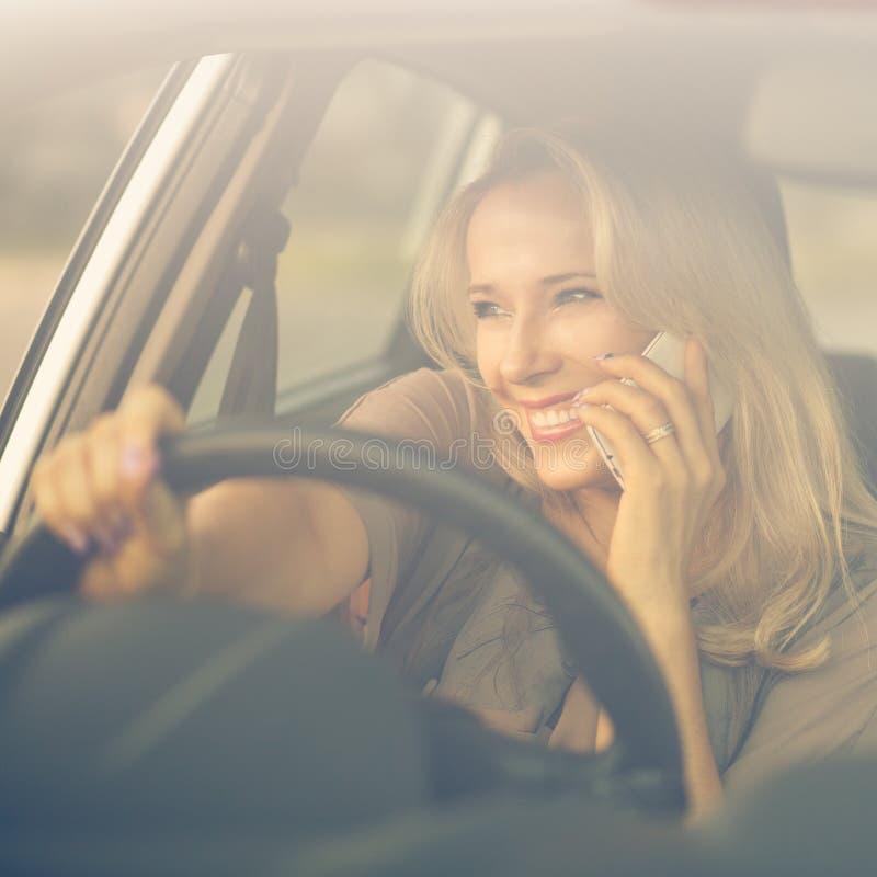 Jeune femme de sourire à l'aide du téléphone dans une voiture images libres de droits