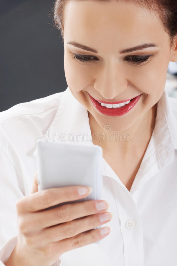 Jeune femme de sourire à l'aide du téléphone portable photos stock
