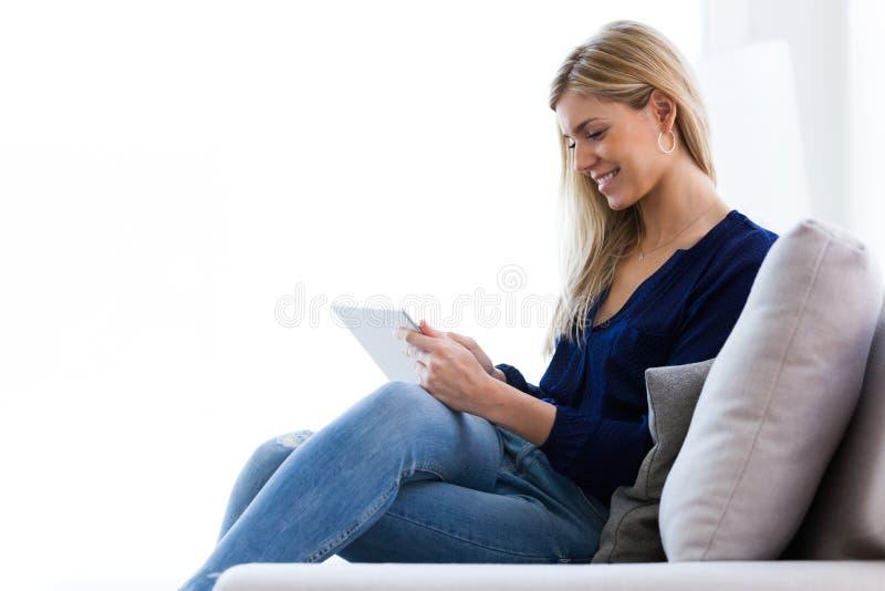 Jeune femme de sourire à l'aide de son comprimé numérique tout en se reposant sur le sofa à la maison photo libre de droits