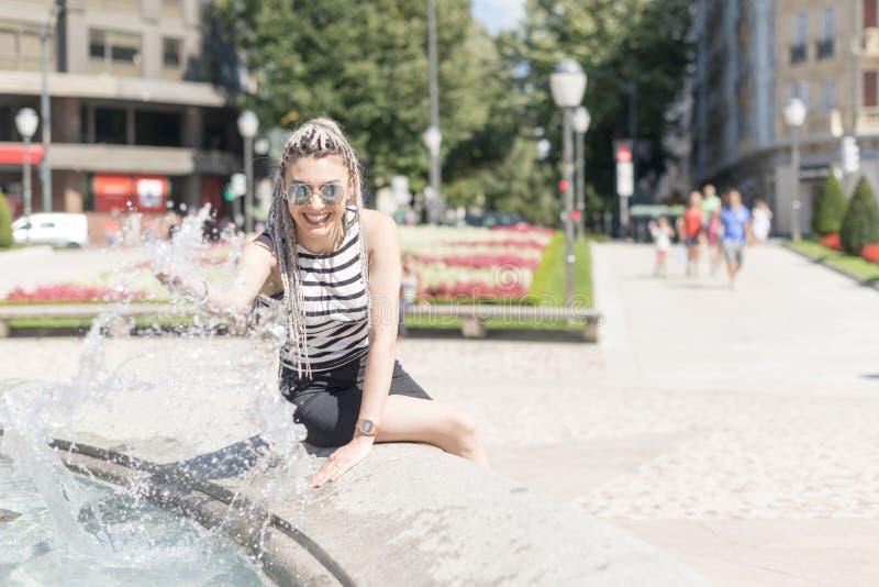 Jeune femme de sourire éclaboussant avec de l'eau images stock
