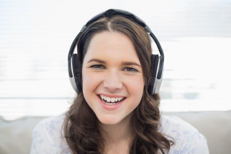 Jeune femme de sourire écoutant la musique images stock