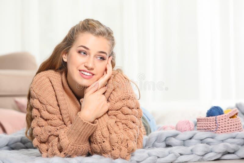 Jeune femme de sourire attirante dans le chandail chaud confortable se trouvant sur le plancher à la maison photos stock