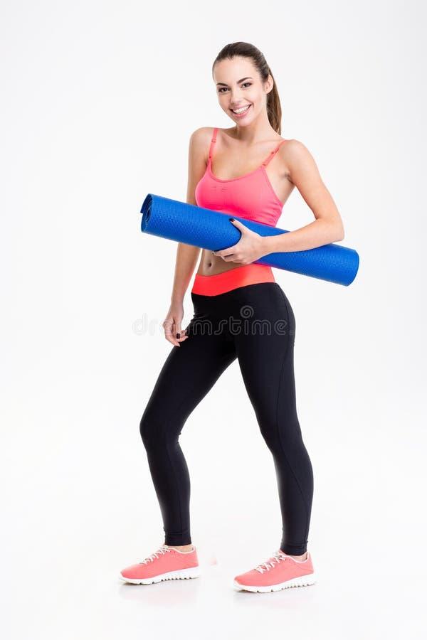 Jeune femme de sourire attirante de forme physique tenant le tapis de yoga image stock