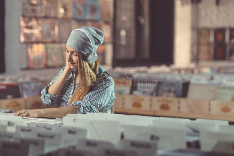 Jeune femme de sourire avec des écouteurs photo libre de droits