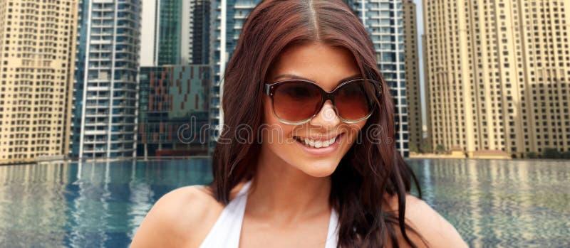 Jeune femme de sourire avec des lunettes de soleil au-dessus de piscine de ville photographie stock libre de droits