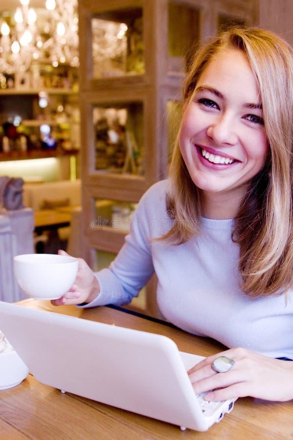 Jeune femme de sourire avec l'ordinateur photographie stock