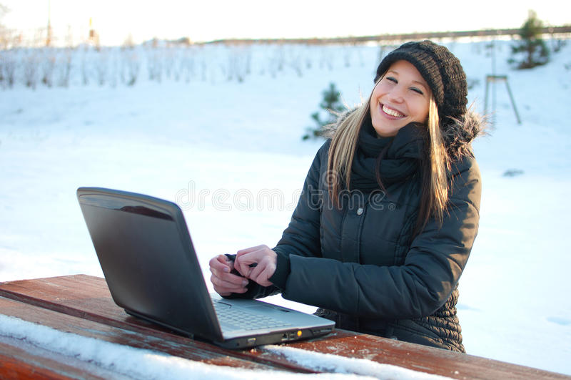 Jeune femme de sourire avec l'ordinateur portatif en hiver photo libre de droits