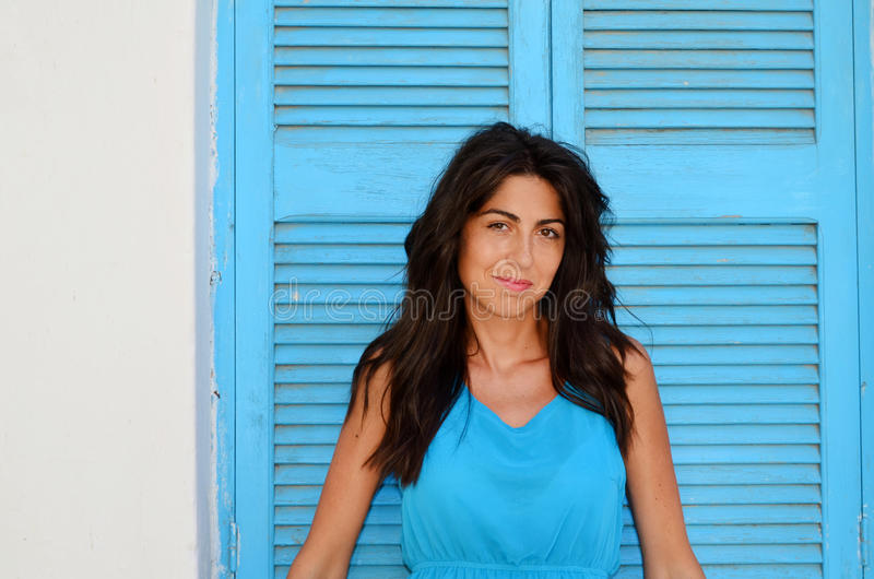 Jeune femme de sourire avec la robe bleue sur un volet bleu en bois photos stock