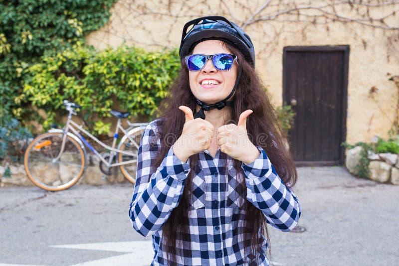 Jeune femme de sourire avec le casque et lunettes de soleil montrant des pouces sur l'allée et la bicyclette de fond photo stock