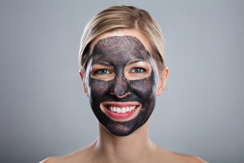 Jeune femme de sourire avec le masque protecteur de charbon actif images stock
