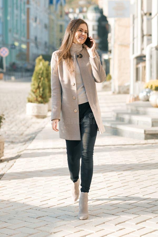 Jeune femme de sourire avec le téléphone portable marchant dans la rue ensoleillée de ville, fille portant le manteau chaud image libre de droits