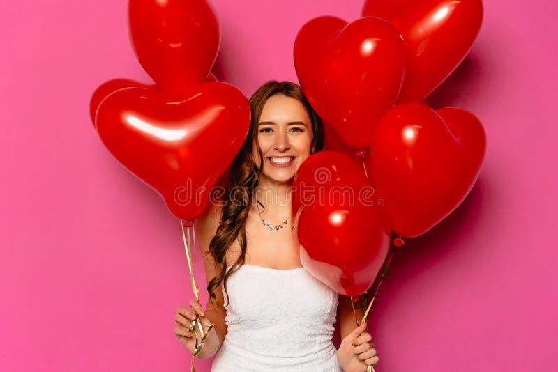 Jeune femme de sourire avec les ballons à air en forme de coeur photographie stock libre de droits