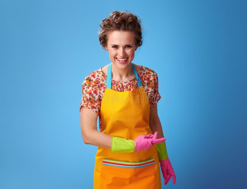 Jeune femme de sourire avec les gants en caoutchouc sur le cintrage bleu photographie stock libre de droits
